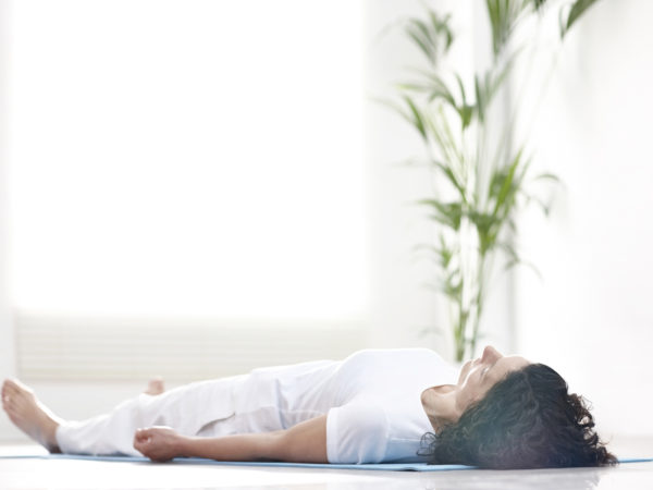 Mature woman lying on a yoga mat and relaxing after workout - Savasana