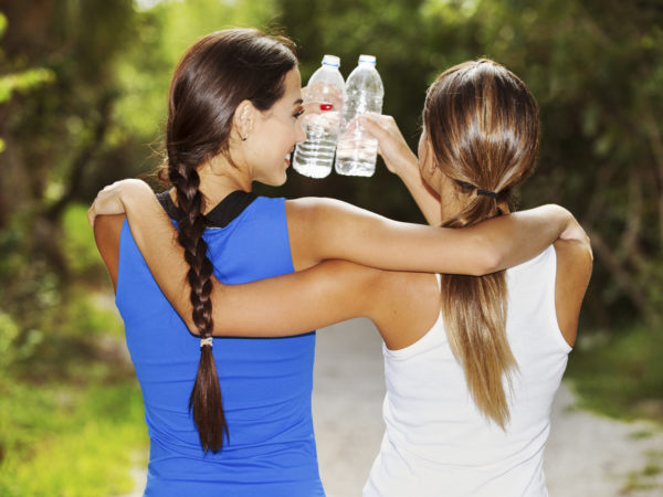 2 young women drinking water after exercise. best friends.