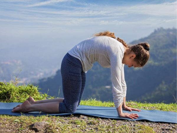 Yoga exercise outdoors - sporty fit woman practices yoga asana Marjariasana - cat pose outdoors in Himalayas