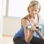 Fit mature woman lifting dumbbell while sitting at home