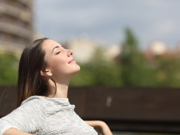 Urban woman sitting on a bench of a park and breathing deep fresh air
