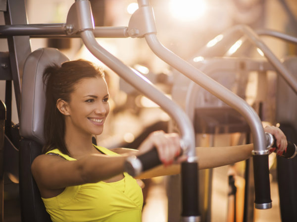 Happy woman working out on exercise machine in a gym.