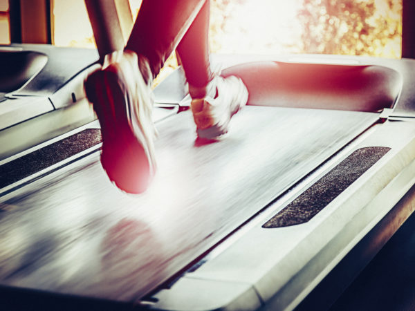 Woman running on treadmill in health club.