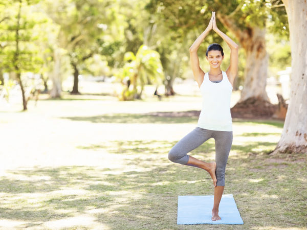 Full length portrait of smiling woman performing yoga in tree pose at park. Horizontal shot.