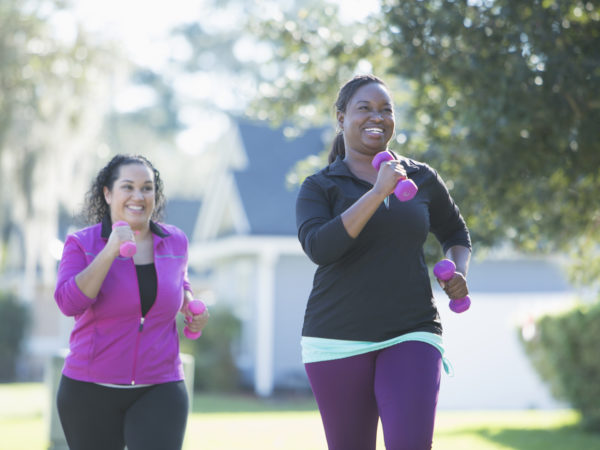 Two multi-ethnic women exercising outdoors, jogging on a sunny day in a residential neighborhood, handweights in their hands. The main focus is on the African American woman, laughing as her Hispanic friend tries to catch up with her.