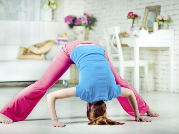 Beautiful young woman doing yoga at home - Prasarita Padottanasana (Wide-Legged Forward Bend)