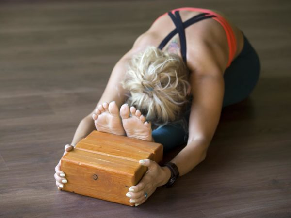 Sporty beautiful young blond woman in sportswear working out indoors, doing exercise for spine, shoulders, hamstrings, sitting in seated forward bend posture, focus on wooden bricks