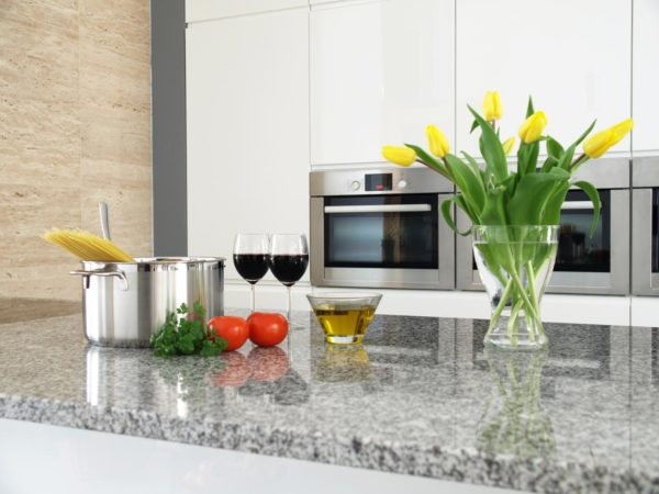 Tomatoes, herbs, wine and flowers on a granite counter top.