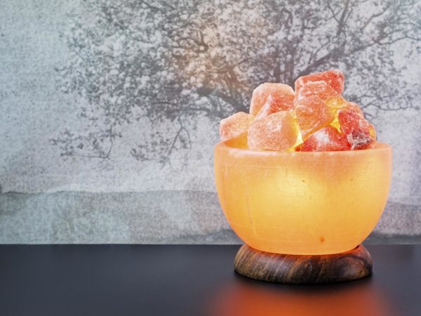 Turned on Himalayan pink salt lamp carved as a bowl on a black table.