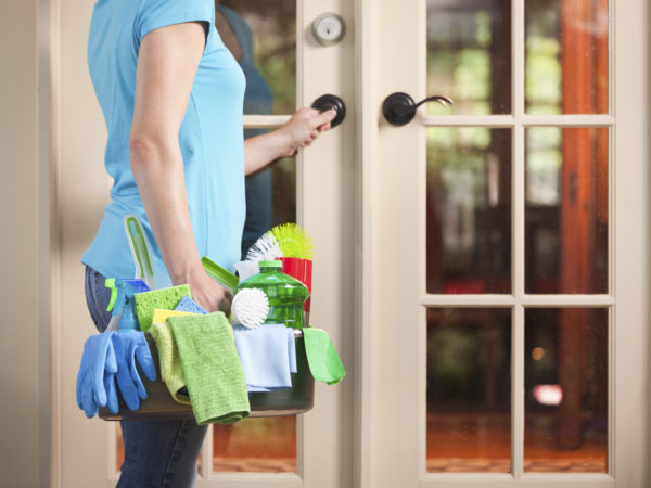 A house spring cleaning service person, a woman maid or cleaner arriving at the door entrance of customer home in the USA. She carries a cleaning kit of tools including rags, cleaning liquids, rubber gloves, and sponges. She wears casual clothes of t-shirt and jeans, arriving for clean-up work.