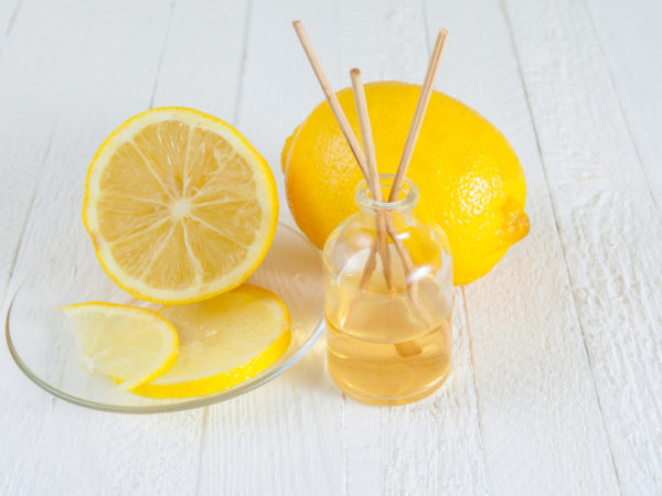 Fragrance sticks or bottle Scent diffuser with Lemon on wooden background.