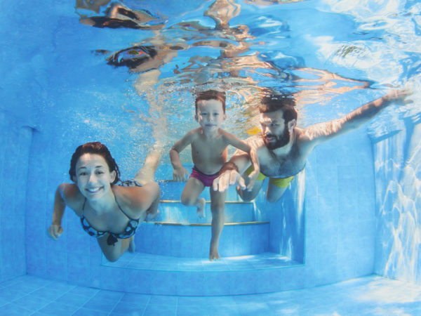 Happy family - father and mother with baby boy swimming and diving underwater with fun in blue pool. Healthy lifestyle, active parents, and people water sports activity on summer vacation with child