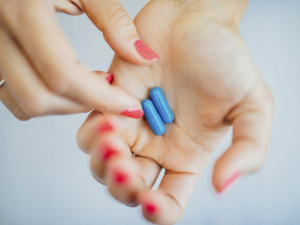 Women's fingers with pink manicure taking blue pills from hands