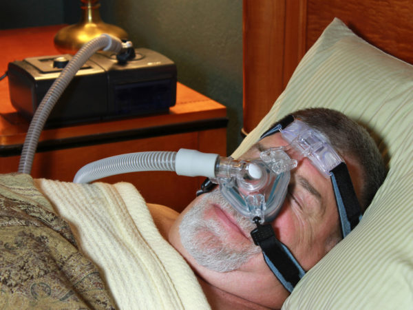A senior man peacefully sleeps with a CPAP mask on his face.