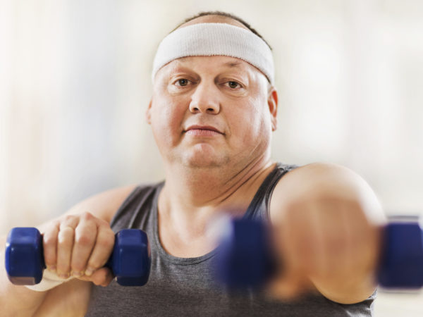 Mid adult overweight man exercising with dumbbells and looking at the camera.