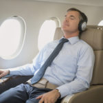 Comfortable business man flying in business class listening to music and relaxing