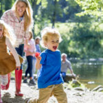 A family are sat at a lake on a nice summers day. The children are running ahead while parents look on.
