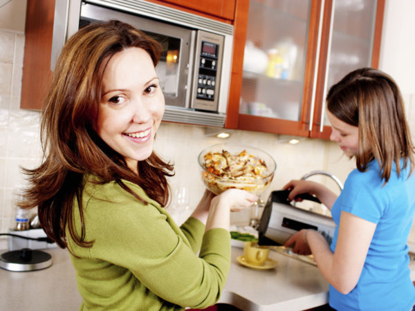 Mother and Daughter cooking, mother putting meal into microwave, girl making tea