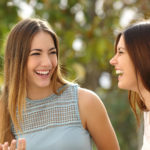 Happy women talking and laughing in a park with a green background