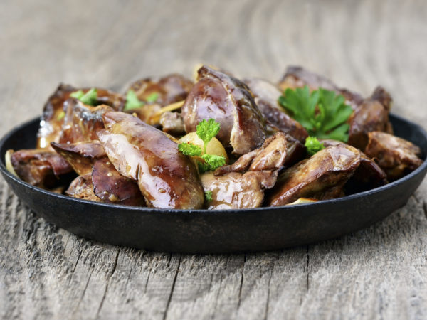 Chicken liver in frying pan on wooden table