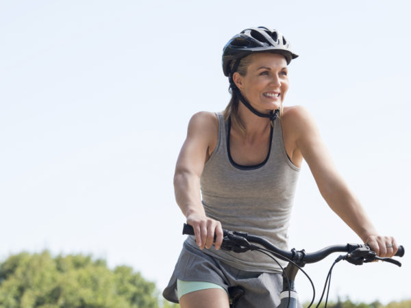 Mature woman riding on mountain bike in the park. Portrait of a happy senior woman riding bicycle in a park. Athletic woman wih helmet cycling and looking away.