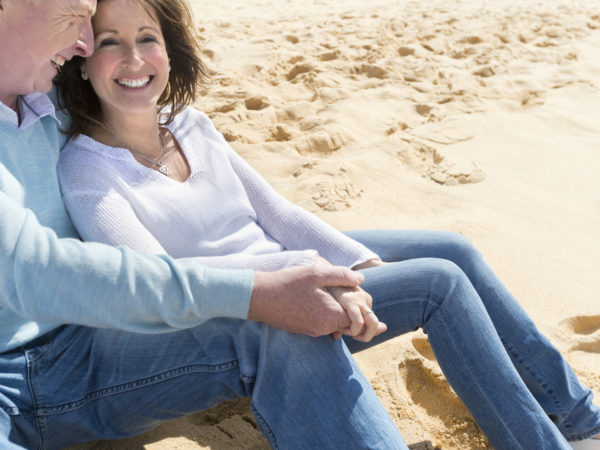 Happy mature couple sitting on the beach holding hands