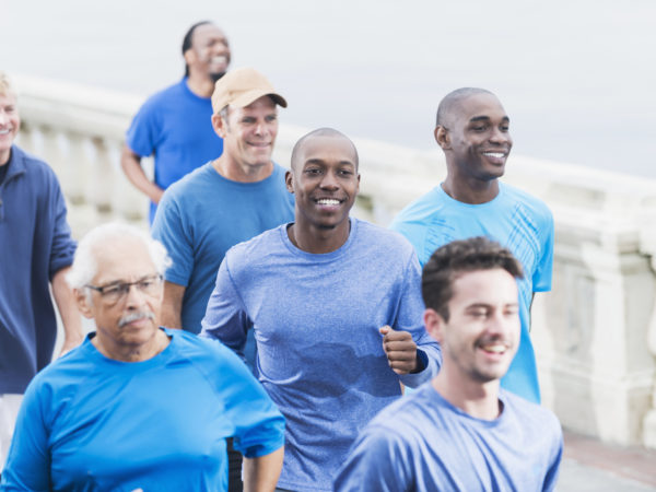 Multi-ethnic group of men wearing blue shirts, running together for a cause.  Focus on young African American man in the center (20s).
