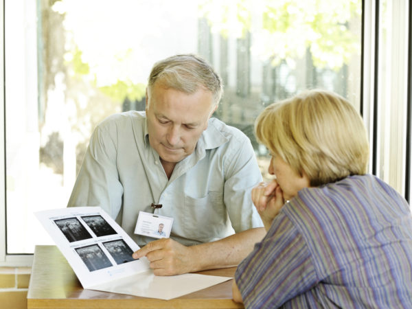 ** ID badge made entirely by photographer ** Specialist doctor explains scans to woman. The scans are blurred for varied use but are actually scans of the uterus for gynaecological tests.