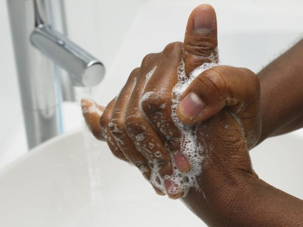 An African American hand washing.  Part of Surgical Scrub Technique for Hand Decontamination