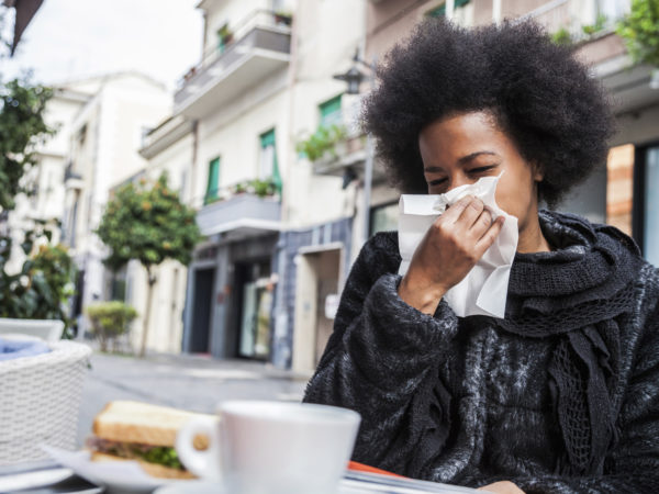 Woman sneezing due to flu during a break in a cafe using an handkerchief