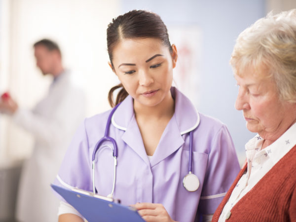 a young nurse stands and chats to a senior woman patient as she leaves the surgery. She is wearing a lilac nursing uniform and holding a clipboard . She is smiling to the senior woman and explaining her treatment plan. In the background a hospital interior can be seen. A male doctor is defocussed in the background.