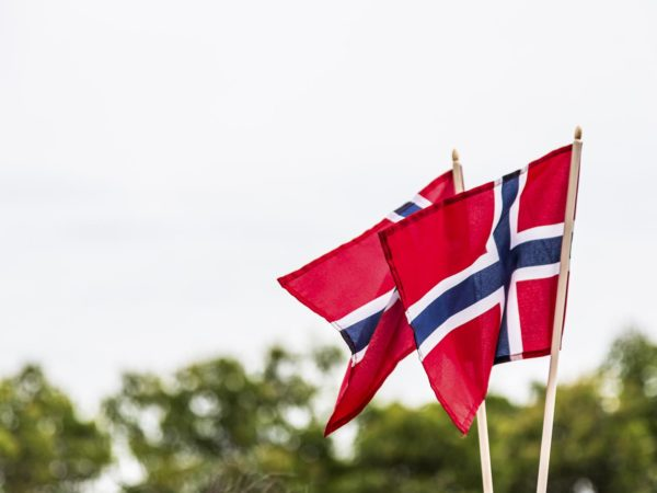 Two Norwegian flags blowing in the wind. The flag of Norway is red with an indigo blue Scandinavian cross fimbriated in white that extends to the edges of the flag&#x3B; the vertical part of the cross is shifted to the hoist side in the style of the Dannebrog, the flag of Denmark.