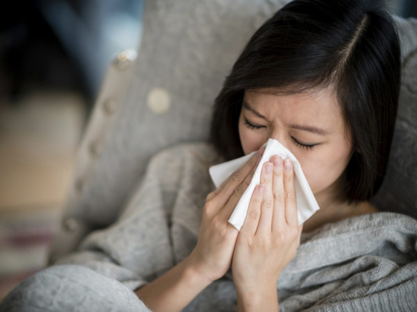 Ill woman with the flu blowing her nose