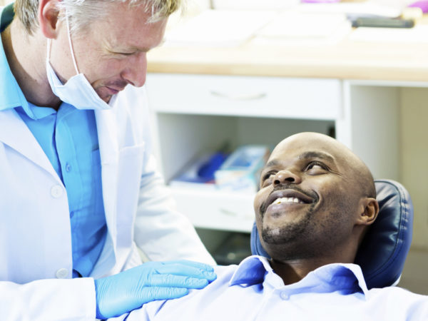 A male patient reclining in the dentist's chair smiles happily up as his dentist looks down at him, patting his shoulder reassuringly.