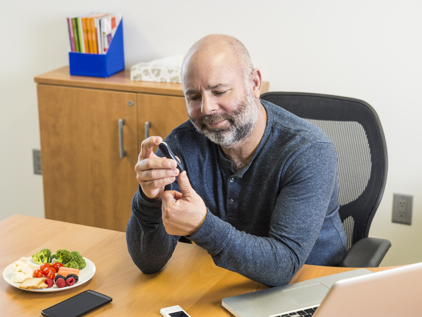 A diabetic man at work testing his blood to monitor his blood glucose levels so he can manage his diabetes.