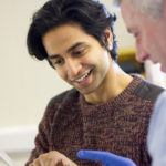 A male doctor  beside another male. They are in an examination room talking as he holds a digital tablet in one hand.  The patient looks happy as he is shown his results by the doctor. very close crop of their head and shoulders.