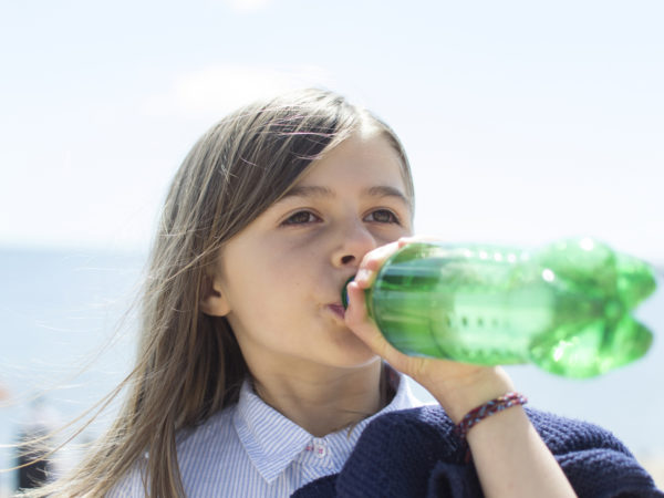 A child drinking a soft drink/pop/soda from a plastic bottle