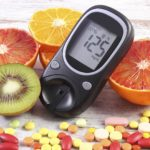 Glucose meter with result of measurement sugar level, fresh natural fruits and medical pills, tablets and supplements, concept of diabetes, healthy lifestyle and nutrition