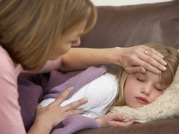 Mother Taking Temperature Of Sick Daughter at home