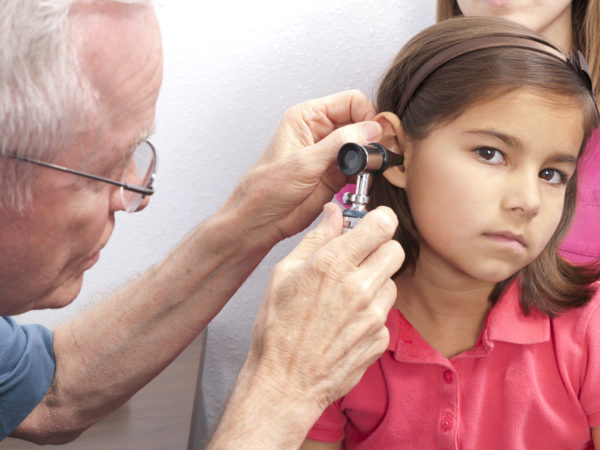"""Stoic, brave young girl allows doctor to look into her ear with otoscope as she sits on her mother's lap.  He could be checking for otitis media, middle ear infection"""