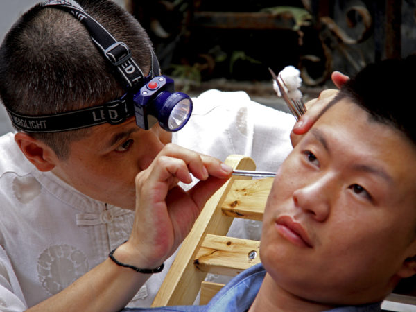 Chengdu, China - August 5, 2013: Ear Wax Removal in Chengdu marketplace