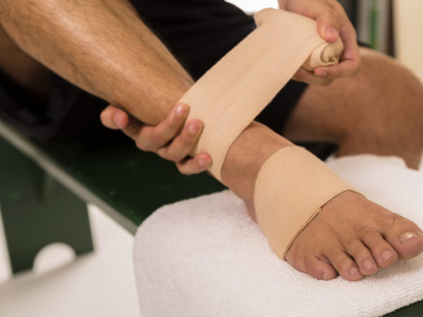 Man in sports locker room wrapping his painful ankle.