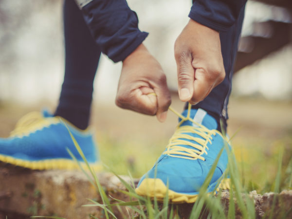 close up of runner tying his shoes preparing for a run a jog outside