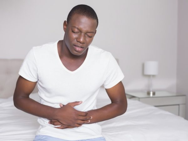 Wincing man sitting on the edge of his bed with a stomach cramp at home in bedroom