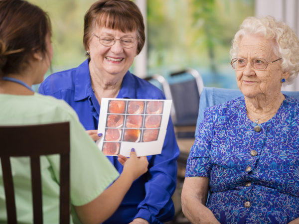 Latin, female doctor or nurse conducts family consultation with elderly patient and her daughter in a nursing home or clinic setting.  They discuss recent colonoscopy results.  Woman is over 100 years old!
