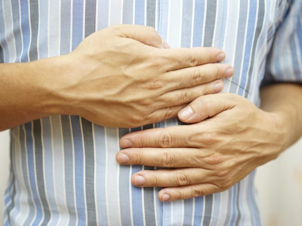 Stomach ache, man placing hands on the stomach, concept of .stomach ulcer
