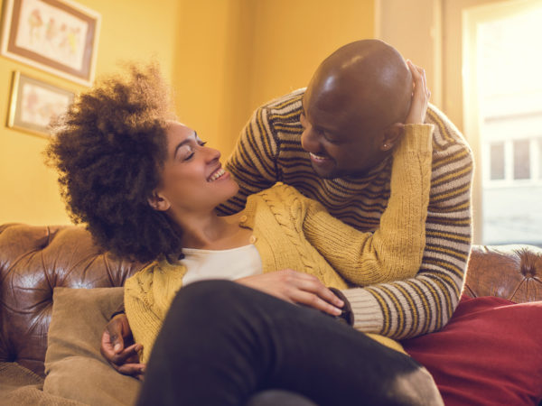 Happy African American couple talking to each other at home. They are full of love toward each other.