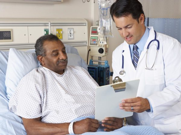 Doctor Explaining Consent Form To Senior Patient Discussing