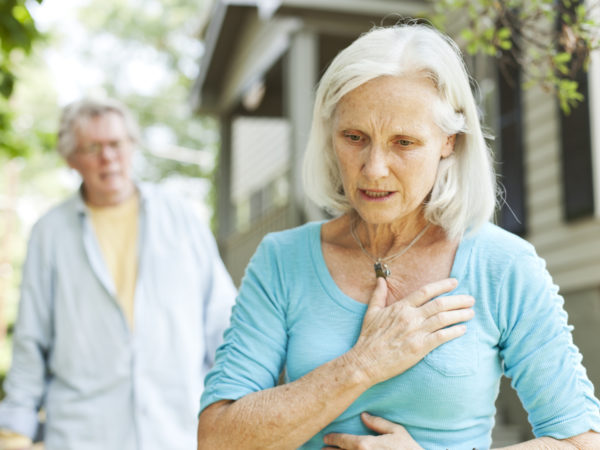 A senior woman experiencing chest pain.  A senior man is in the background.