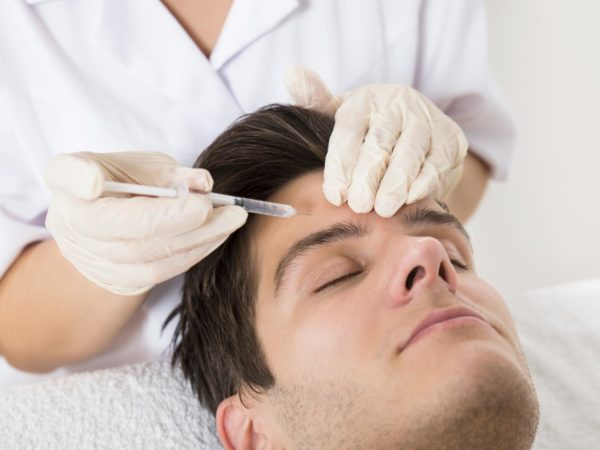 Young Man Having Botox Treatment At Beauty Clinic